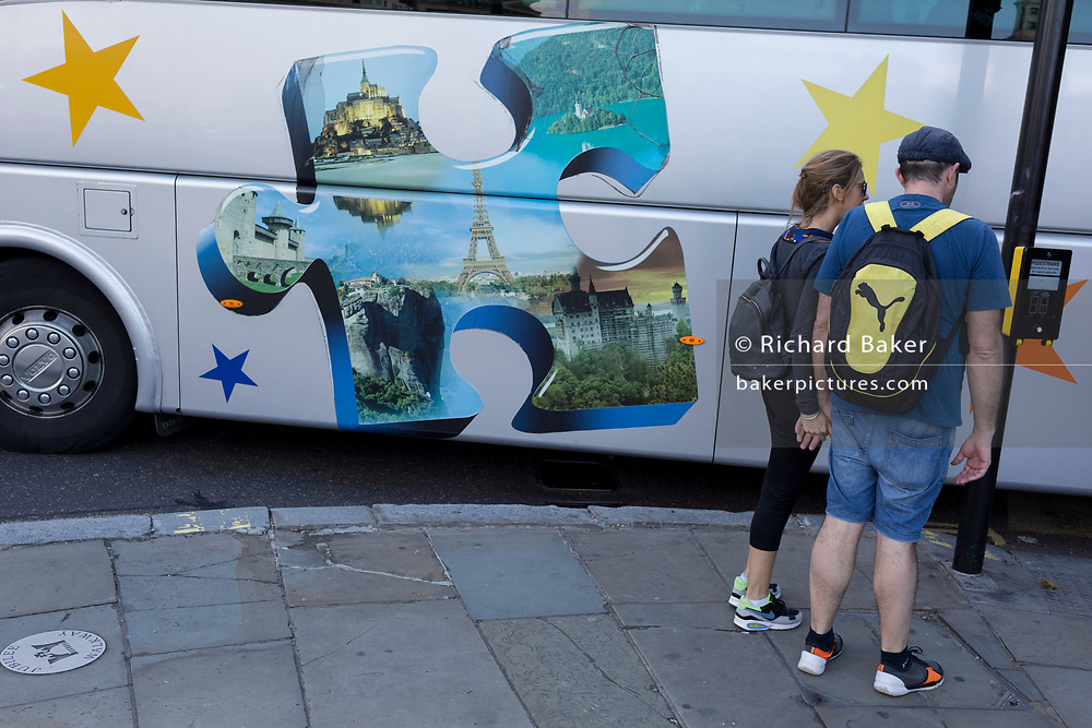 A tour coach showing European destinations passes tourists in Trafalgar Square, on 10th August 2017, in London, England.