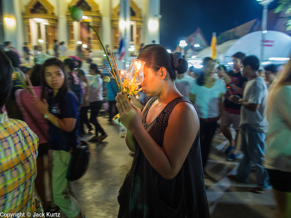 """13 MAY 2013 - BANGKOK, THAILAND:  A woman carries a candle lantern during Vesak services at Wat That Thong in Bangkok. Vesak, called Wisakha Bucha in Thailand, is one of the most important Buddhist holy days celebrated in Thailand. Sometimes called """"Buddha's Birthday"""", it actually marks the birth, enlightenment (nirvana), and death (Parinirvana) of Gautama Buddha in the Theravada or southern tradition. It is also celebrated in Cambodia, Laos, Myanmar, Sri Lanka and other countries where Theravada Buddhism is the dominant form of Buddhism.    PHOTO BY JACK KURTZ"""
