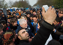 © Licensed to London News Pictures. 23/01/2016. Dunkirk, France. A migrant takes a selfie as Leader of the Labour Party JEREMY CORBYN (centre) visits a temporary camp in Dunkirk, France, where thousands of migrants and refugees attempting to reach the UK are currently living. Photo credit: Ben Cawthra/LNP
