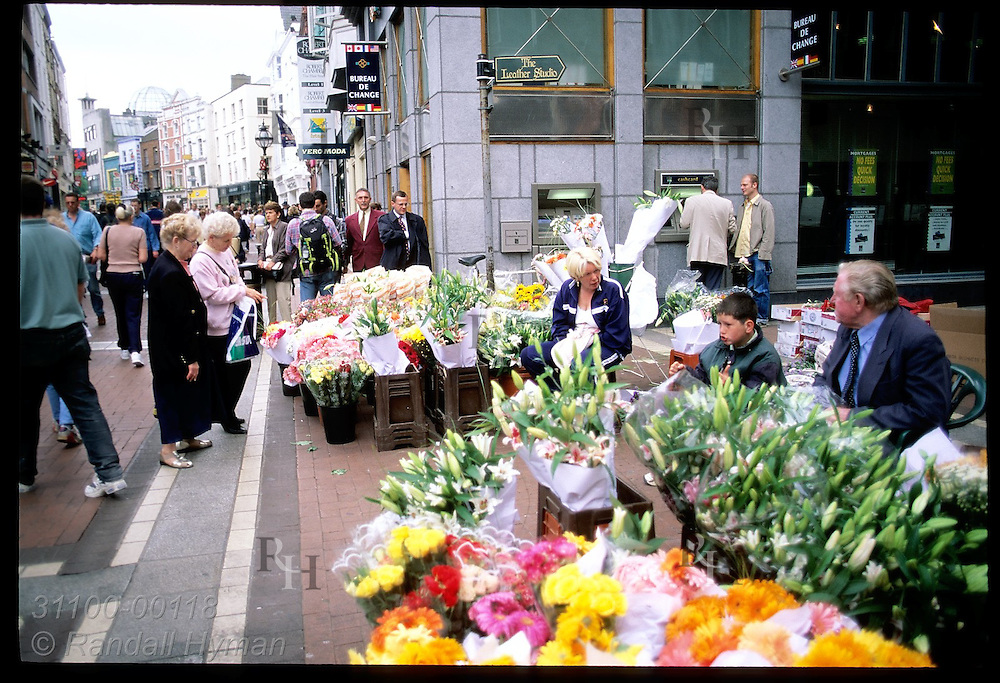 Pedestrians pass bins of flowers on busy Grafton Street, posh walking mall in downtown Dublin. Ireland