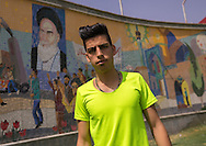 Iran, Tehran province, Tehran, young man with western haircut in the bazaar. This hairdo violates the Islamic system's regulations. A giant fresco showing Ayatollah Khomeini can be seen in the background.