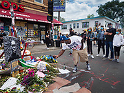 "12 JUNE 2020 - MINNEAPOLIS, MINNESOTA: A man takes pictures with his cell phone at the impromptu memorial for George Floyd at the corner of 38th Street and Chicago Ave. in Minneapolis. The intersection is informally known as ""George Floyd Square"" and is considered a ""police free zone."" There are memorials to honor Black people killed by police and people providing free food at the intersection. Floyd, an unarmed Black man, was killed by Minneapolis police on May 25 when an officer kneeled on his neck for 8 minutes and 46 seconds. Floyd's death sparked weeks of ongoing protests and uprisings against police violence around the world.          PHOTO BY JACK KURTZ"