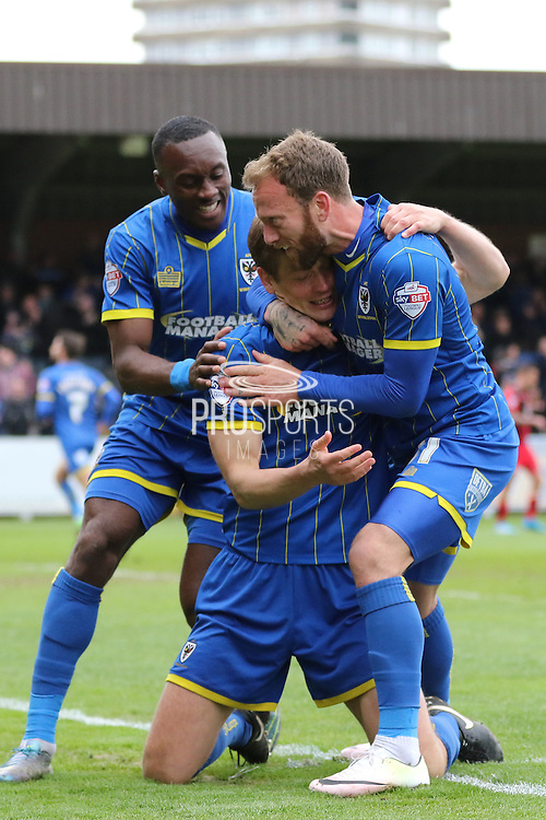 Sean Rigg forward for AFC Wimbledon (11), Ade Azeez forward for AFC Wimbledon (14) and Paul Robinson defender for AFC Wimbledon (6) celebrate the winning goal during the Sky Bet League 2 match between AFC Wimbledon and Crawley Town at the Cherry Red Records Stadium, Kingston, England on 16 April 2016. Photo by Stuart Butcher.