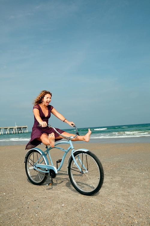 Sasha B. rides her bike on the beach.