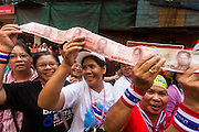 01 FEBRUARY 2014 - BANGKOK, THAILAND: Thai anti-government protestors hold up a line of cash they were waiting to donate to Suthep Thaugsuban. The anti-government protest movement, led by the People's Democratic Reform Committee (PDRC) organized a march through the Chinatown district of Bangkok Saturday and disrupted the city's famous Chinese New Year festival. Some streets were blocked and protest leader Suthep Thaugsuban walked through the neighborhood collecting money. The march was in advance of massive protests the PDRC has promised for Sunday, Feb. 2 in an effort to block Thais from voting in the national election.     PHOTO BY JACK KURTZ