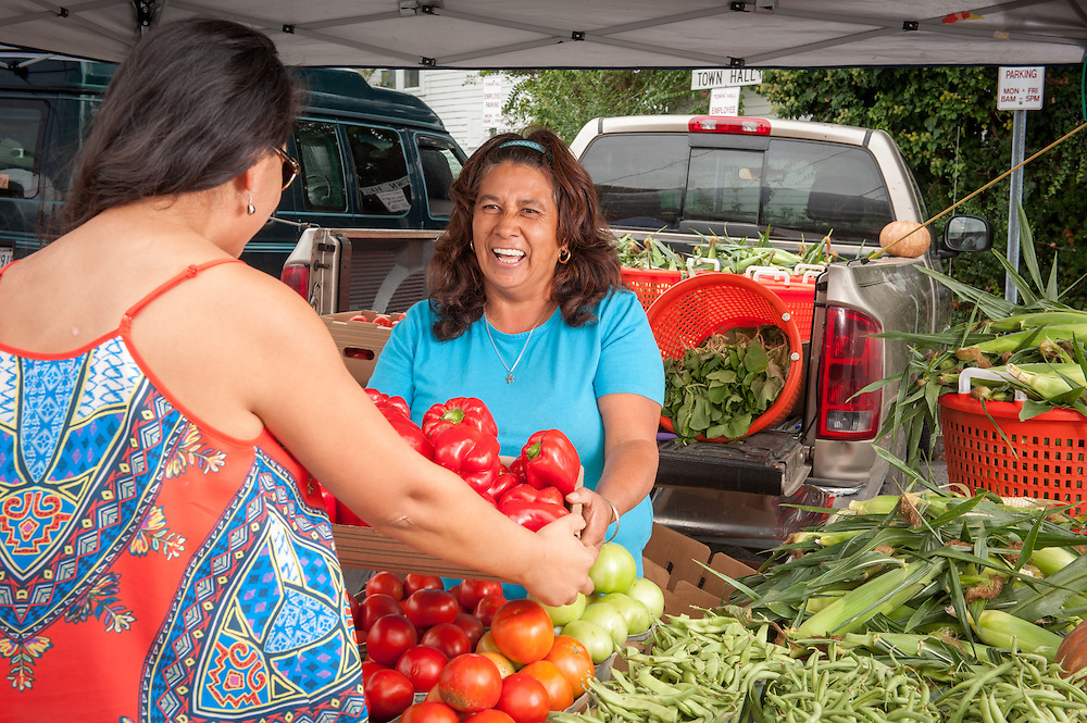 A Hispanic woman selling vegetables and other produce at a farmer's market on Maryland's Eastern shore.