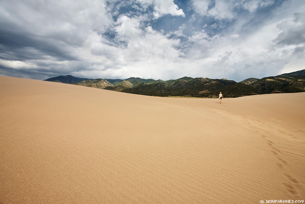 A woman explores the vastness of Great Sand Dunes National Park in the San Luis Valley of Colorado.