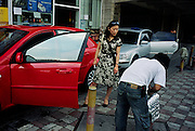 A woman watches as her car is washed and detailed. Shanghai, China, Wed Oct. 4, 2006.