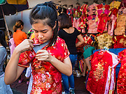 """31 JANUARY 2016 - BANGKOK, THAILAND: A woman tries on a traditional dress while she shops for new clothes at a stand on Yaowarat Road, in Bangkok's Chinatown district, before the celebration of the Lunar New Year. Chinese New Year, also called Lunar New Year or Tet (in Vietnamese communities) starts Monday February 8. The coming year will be the """"Year of the Monkey."""" Thailand has the largest overseas Chinese population in the world; about 14 percent of Thais are of Chinese ancestry and some Chinese holidays, especially Chinese New Year, are widely celebrated in Thailand.             PHOTO BY JACK KURTZ"""