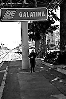 un'anziana passeggia lungo la banchina della stazione. Reportage che analizza le situazioni che si incontrano durante un viaggio lungo le linee ferroviarie delle Ferrovie Sud Est nel Salento
