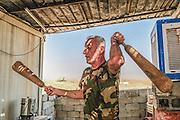 As a morning fitness workout, a Peshmerga fighter swings the wooden Zurkhaneh batons, a power exercise of Iranian origin, dating to 550 B.C.. Mount Batiwa frontline. Iraqi Kurdistan.