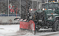 Middletown, NY - A  snowplow drives passt a mechanical Santa in the window of a store as snow falls during a winter storm on Dec. 19, 2008.