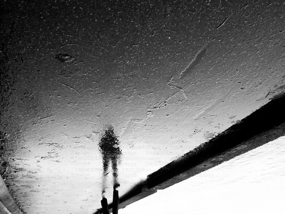 An inverted reflection of a person walking along a seawall.