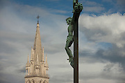 A crucified Christ on the cross looking down on the tall spire of Eglise St Anne (church) in Montpellier, south of France.