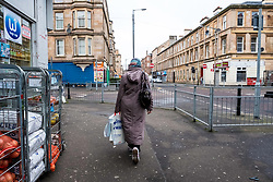 Muslim woman walking street in Govanhill district of Glasgow, Scotland, United Kingdom