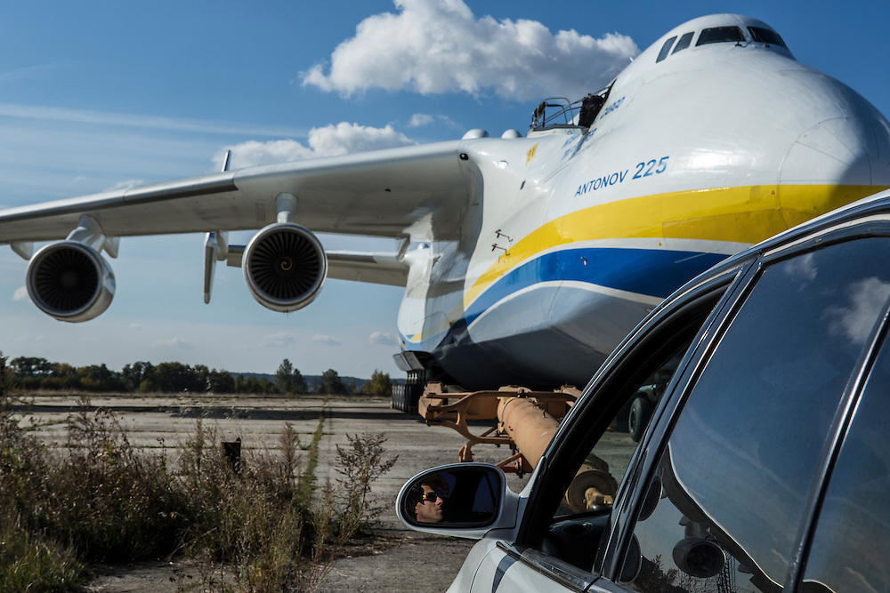 GOSTOMEL, UKRAINE - OCTOBER 1, 2014: A company driver sits in his car near the Antonov AN-225, the longest and heaviest airplane ever built, on an airfield in Gostomel, outside Kiev, Ukraine. CREDIT: Brendan Hoffman for The New York Times