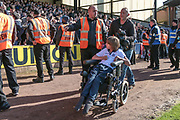 A disabled Bolton Wanderers fan is helped out of the crowd to safety as the police and stewards regain control and get the fans back into the stands during the EFL Sky Bet League 1 match between Port Vale and Bolton Wanderers at Vale Park, Burslem, England on 22 April 2017. Photo by Mark P Doherty.