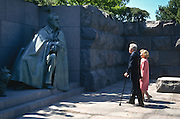 President Bill Clinton on crutches and First Lady Hillary pause to view the sculpture of Franklin D. Roosevelt after the opening ceremony of the FDR Memorial May 2, 1997 in Washington, DC. The memorial to the US 32nd president spreads across four granite-walled outdoor rooms along a 7.5 acre-swath of West Potomac Park.