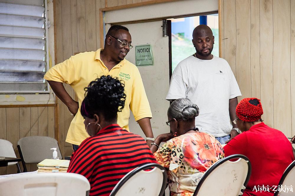 Patrick Anthony and Joseph Pierre check-in to vote at Charlotte Amalie High School.  8 September 2012.  © Aisha-Zakiya Boyd