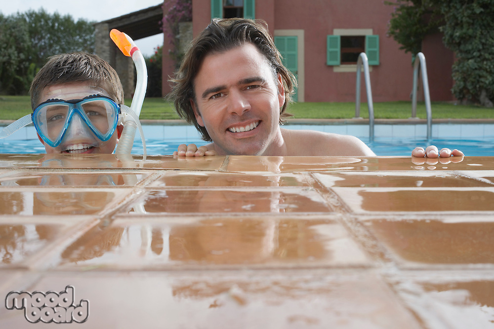 Portrait of father and son (10-12) in pool boy in snorkelling mask smiling