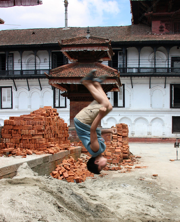 Boy jumps over bricks, Kathmandu, Nepal
