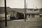 USA, Arlizona, Kingman. A freight train passes through an abandoned train station.