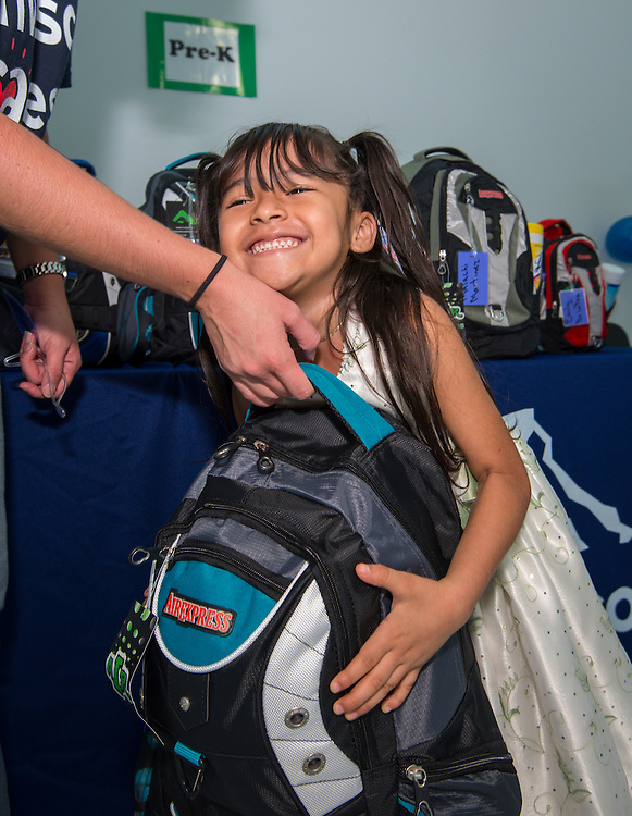 Students receive school supplies donated by Invesco at the Rusk School, August 22, 2014.