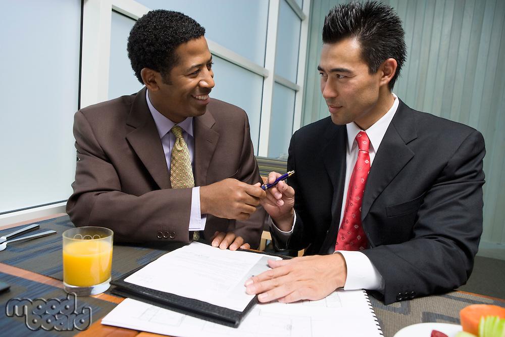 Businessman handing pen over to another businessman
