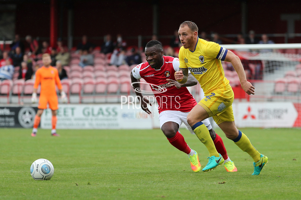 AFC Wimbledon defender Barry Fuller (2) battles for possession with Ebbsfleet united  attacker Aaron McLean (10) during the Pre-Season Friendly match between Ebbsfleet and AFC Wimbledon at Stonebridge Road, Ebsfleet, United Kingdom on 29 July 2017. Photo by Matthew Redman.