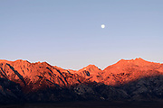 Golden light sunrise and full moon over Trojan Peak in the Alabama Hills near Lone Pine, California, USA,
