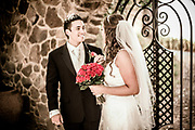 Bride holding red roses and groom looking at her lovingly with a rock wall background