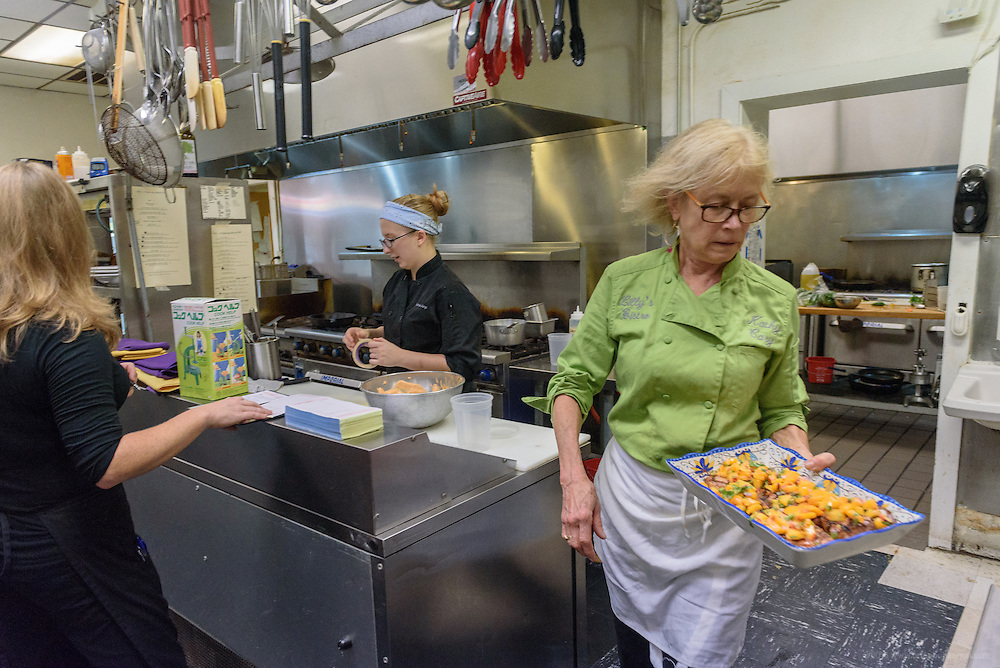 Chef Kathy Cary carries a fresh dish to the La Peche gourmet-to-go case. Lunchtime in the kitchen at Lilly's Monday, Aug. 15, 2016 with Chef/Owner Kathy Cary and staff. (Photo by Brian Bohannon)