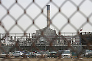 industrial electric plant seen through a fence with parked cars