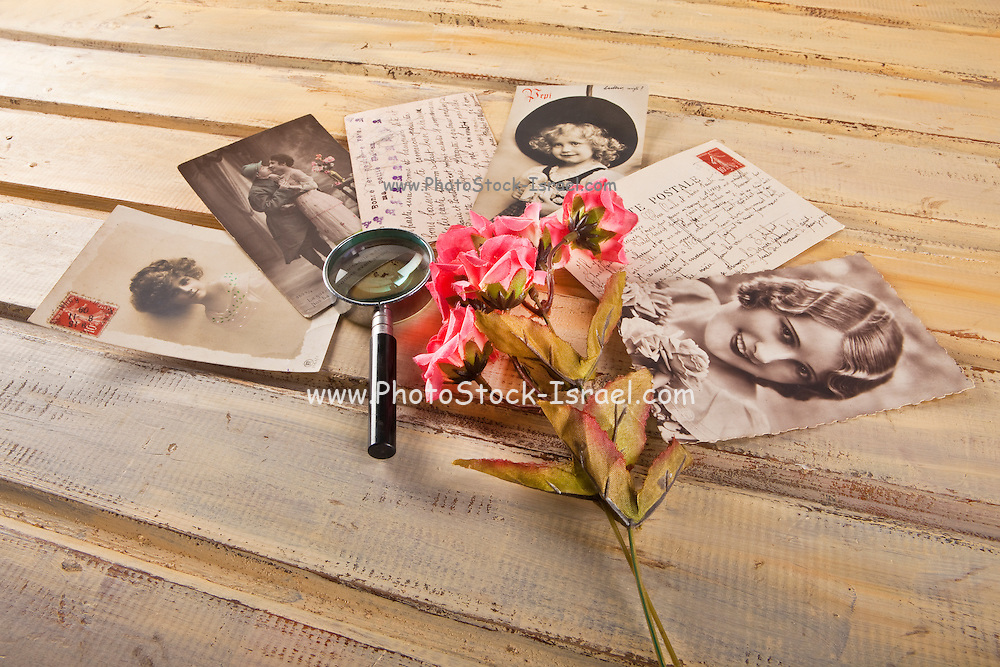 Retro Style atmospheric image with old style picture postcards and a magnifying glass