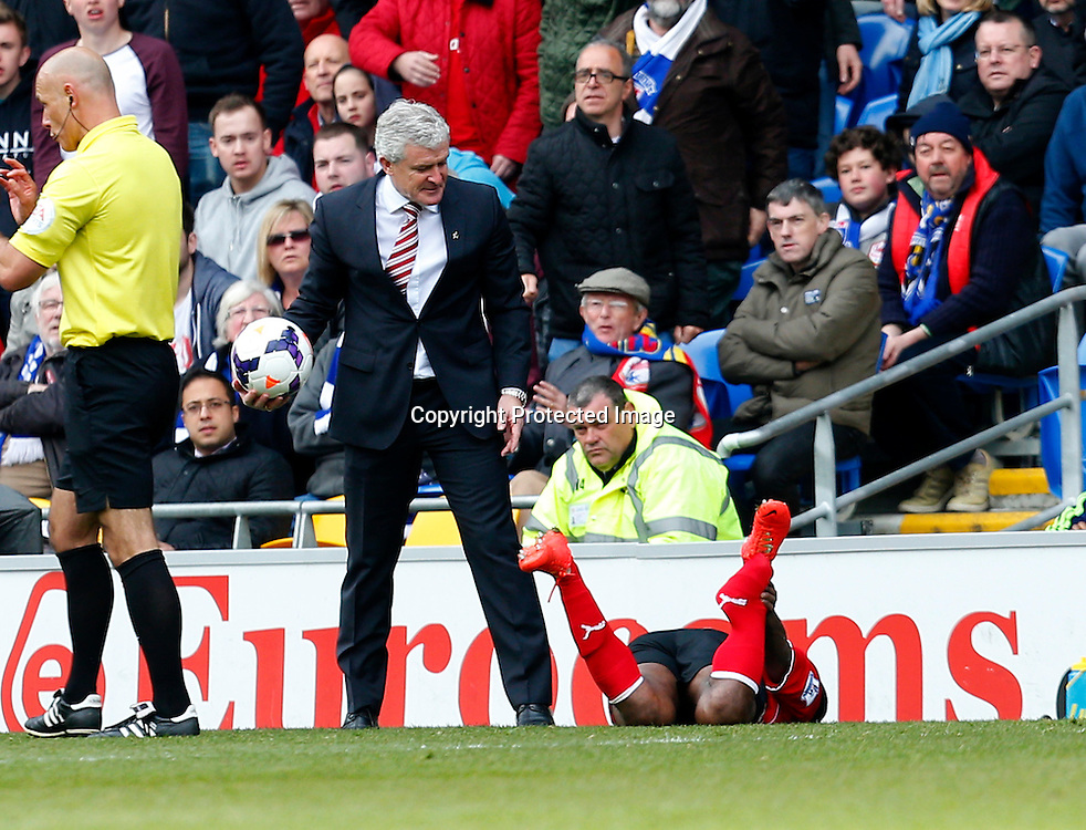 19th April 2014 Barclays Premier League Football - Cardiff City v Stoke City - Stoke manager Mark Hughes casts a accusing look at a fouled Cardiff player. Paul Roberts/Offside