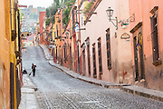 A woman sweeps the cobblestones along Cuadrante Street in the historic center of San Miguel de Allende, Mexico.