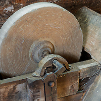 An old grindstone captured in warm afternoon light.