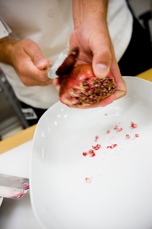 Brookshires grocery executive chef Glenn Terrell deconstructs a pomegranate on Monday, September 14, 2009. Terrell uses a three step process to extract the pomegranate seeds from the rind; cut in half, strike with a spoon and serve.  Photo By Tom Turner