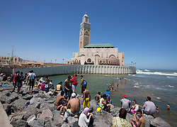 © Licensed to London News Pictures. 23/06/2013. Casablanca,  Morrocco. Young men and boys challenge each other to leap of a 25m cliff edge set against the Hassan II mosque, the fifth largest mosque in the world.   Photo credit: Alison Baskerville/LNP