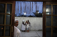 RIO DE JANEIRO, BRAZIL - JANUARY 24: Practitioners linger before a candomble ceremony, in Rio de Janeiro, Brazil, on Saturday, Jan. 23, 2015. Brazil's Afro-Brazilian religions which in recent years have come under increasing threats and prejudice, particularly from the growing number of evangelical churches. Candombl&eacute; originated in Salvador, Bahia at the beginning of the 19th century when enslaved Africans brought their beliefs with them. Umbanda and candombl&eacute; are Afro-Brazilian religions practiced in mostly Brazil. <br /> (Lianne Milton for the Washington Post)