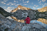 Adult male hiker in red jacket admired the view of Mount Regan mirrored in still waters of Sawtooth Lake at sunrise. Sawtooth Mountains Wilderness Idaho