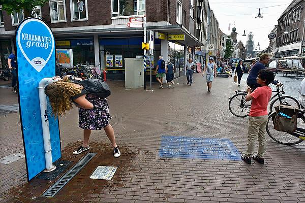 Nederland, Nijmegen, 12-7-2014Recreatie, ontspanning in de stad aan de rivier Waal tijdens de zomerfeesten. De vierdaagsefeesten zijn het grootste evenement van Nederland. Een vrouw drinkt gratis water aan een waterpunt, watertappunt met schoon kraanwater, drinkwater, drinken van vitens.Foto: Flip Franssen/Hollandse Hoogte