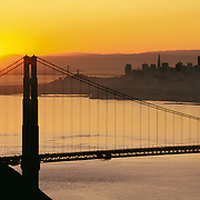 Golden Gate Bridge at sunrise with San Francisco California skyline and Bay Bridge in background