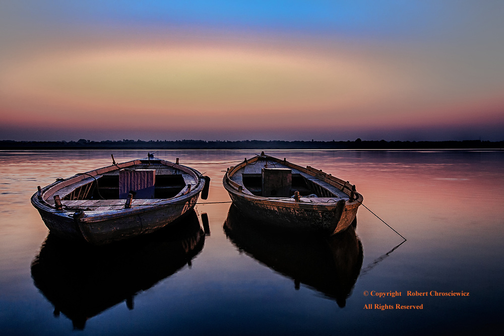 Dawn Delight: Dawn breaks over two deserted wooden boats that rest, moored riverside on the still Ganges River, Varanasi India.