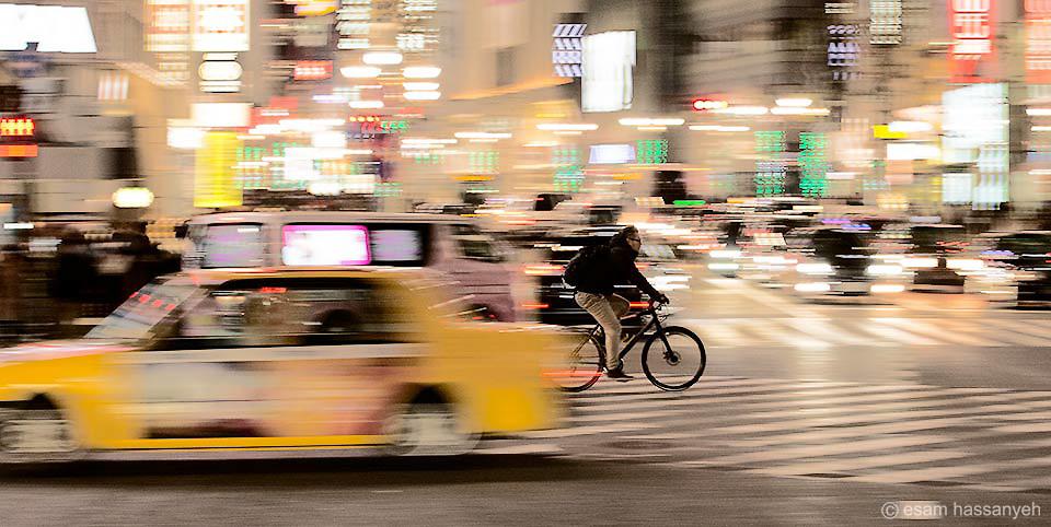 A cyclist speeds through the Shibuya crossing in Tokyo.