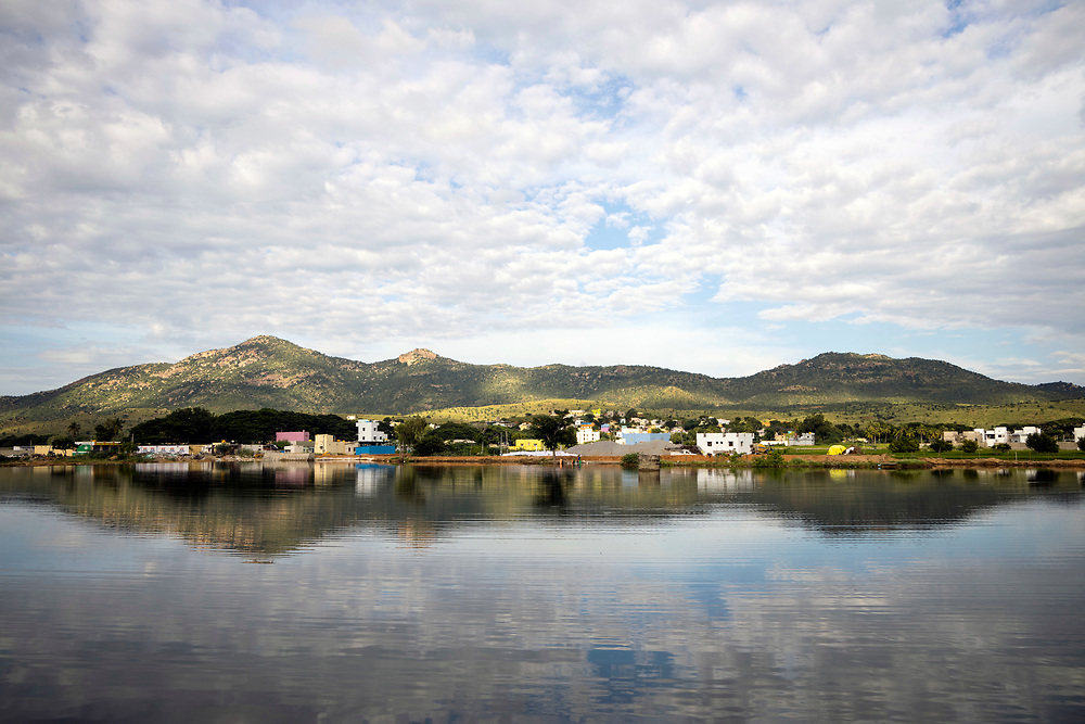 PUTTARPATHI, INDIA - 27th October 2019 - Village surrounding Puttaparthi reflected in lake with cloudy blue sky background, Andhra Pradesh, South India.