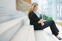 Businesswoman text messaging on steps outside office