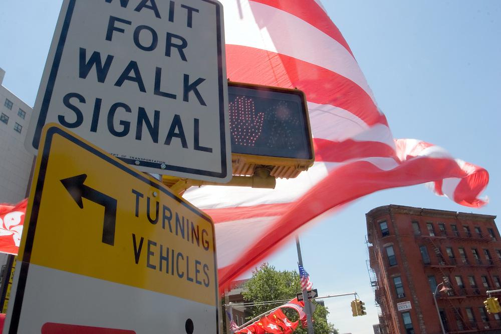 Una bandera americana ondea al viento junto a varias señales de tráfico en una intersección de calles en Chinatown, en Manhattan.