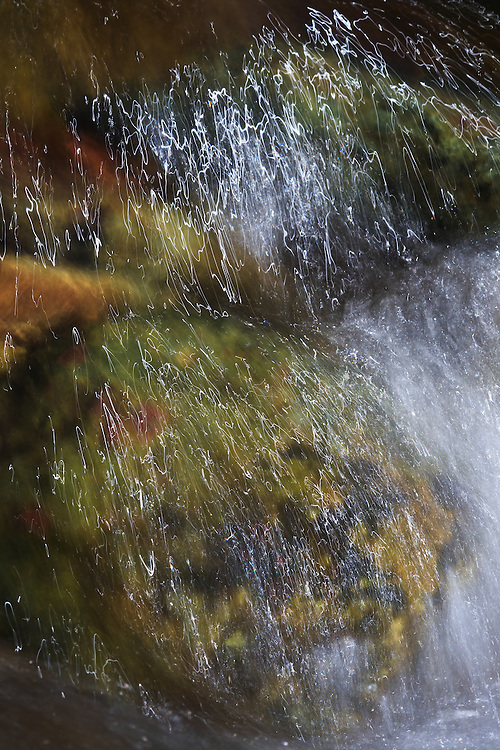 A small cascade over submerged rocks is lit by afternoon light, Rose River, Shenandoah National Park, Virginia.