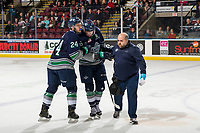 KELOWNA, CANADA - JANUARY 30:  Seattle Thunderbirds' athletic therapist Phil Varney and Jake Lee #24 escort Noah Philp #16 of the Seattle Thunderbirds to the bench during first period against the Kelowna Rockets on January 30, 2019 at Prospera Place in Kelowna, British Columbia, Canada.  (Photo by Marissa Baecker/Shoot the Breeze)